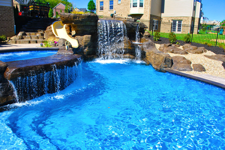 In Ground Concrete Pool with Waterfall and Stamped Concrete Patios.